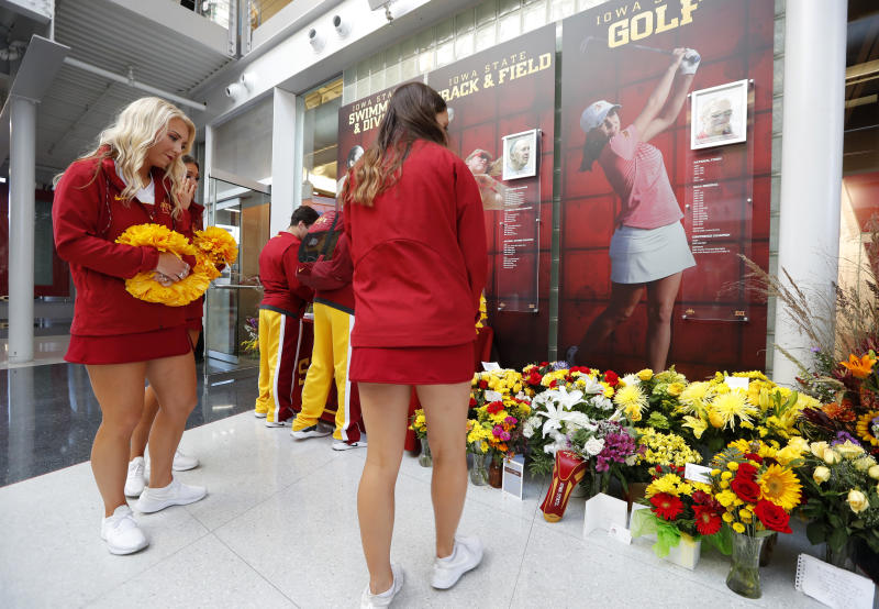 Iowa State cheerleaders look at a memorial to honor slain student Celia Barquin Arozamena, seen in photo at right, before an NCAA college football game between Iowa State and Akron, Saturday, Sept. 22, 2018, in Ames, Iowa. Barquin, who was the 2018 Big 12 women's golf champion and Iowa State Female Athlete of the Year, was found Monday morning in a pond at a golf course near the Iowa State campus. (AP Photo/Charlie Neibergall)