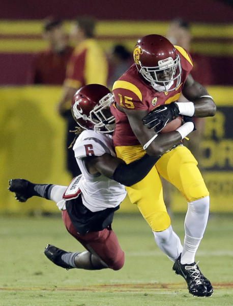 Washington State cornerback Damante Horton, left, brings down Southern California wide receiver Nelson Agholor during the first half of an NCAA college football game in Los Angeles, Saturday, Sept. 7, 2013. (AP Photo/Chris Carlson)