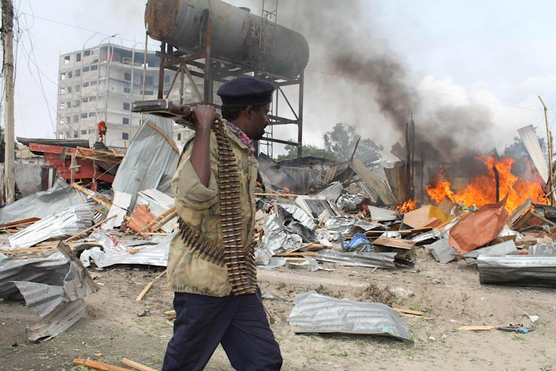 A Somali soldier walks near burning houses near the United Nations building after a suicide bomber detonated his explosives near a moving convoy of African union troops in Mogadishu, Somalia, Friday, July, 12, 2013. Police have said that at least two people were killed and seven were injured in the blast. (AP Photo/Farah Abdi Warsameh)