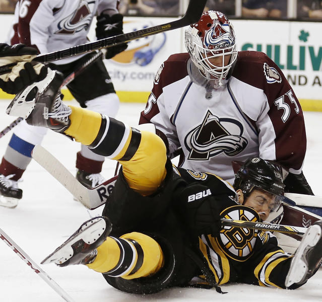 Boston Bruins' Chris Kelly is sent to the ice in front of Colorado Avalanche goalie Jean-Sebastien Giguere during the second period of an NHL hockey game in Boston on Thursday, Oct. 10, 2013. (AP Photo/Winslow Townson)