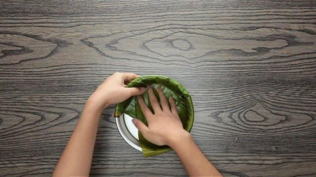 Folding banana leaf down into a round baking tin
