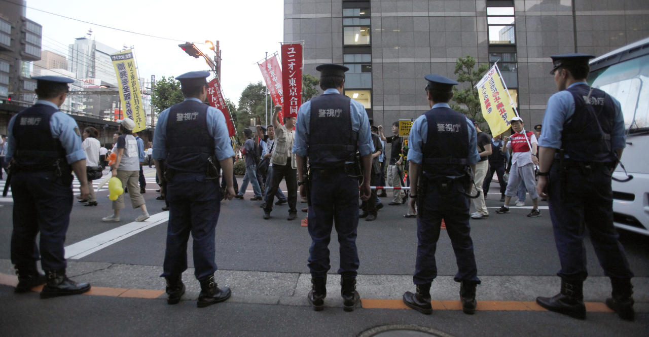Police officers stand in front of the headquarters of Tokyo Electric Power Co., the operator of tsunami-hit Fukushima Dai-ichi nuclear plant, as a group of demonstrators walk by the building during their anti-nuclear power protest march in Tokyo Thursday, June 30, 2011. (AP Photo/Shizuo Kambayashi)
