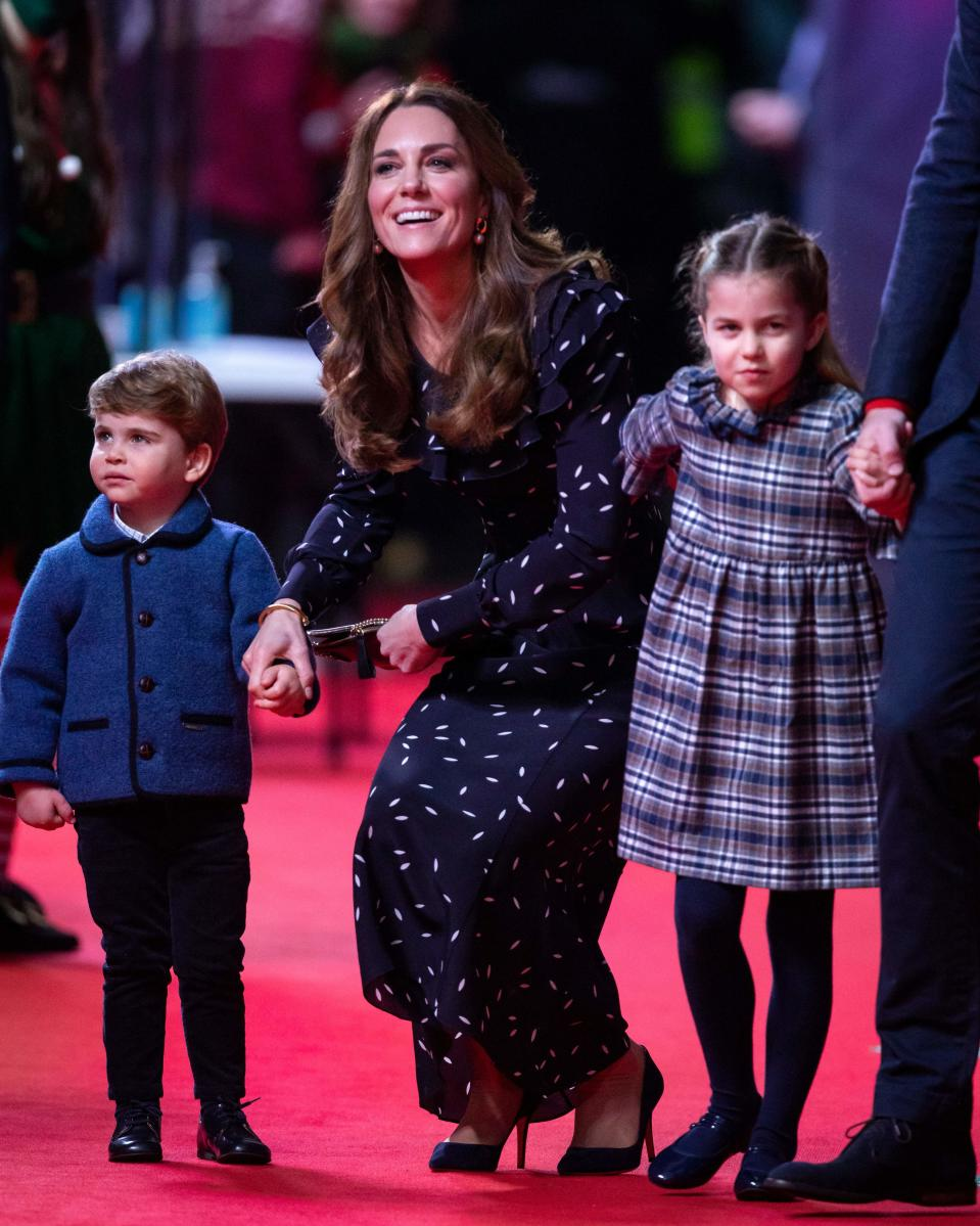 Britain's Catherine, Duchess of Cambridge (C), holds the hand of her son, Britain's Prince Louis of Cambridge (L) and her daughter Britain's Princess Charlotte of Cambridge (R) as they attend a special pantomime performance of The National Lotterys Pantoland  at London's Palladium Theatre in London on December 11, 2020, to thank key workers and their families for their efforts throughout the pandemic. (Photo by Aaron Chown / POOL / AFP) (Photo by AARON CHOWN/POOL/AFP via Getty Images)