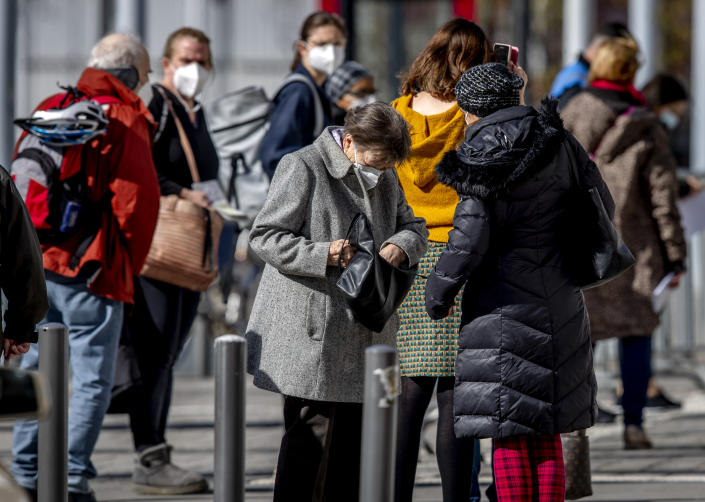 People wear face masks as they queue in front of the vaccination center in Frankfurt, Germany, Monday, March 29, 2021. (AP Photo/Michael Probst)