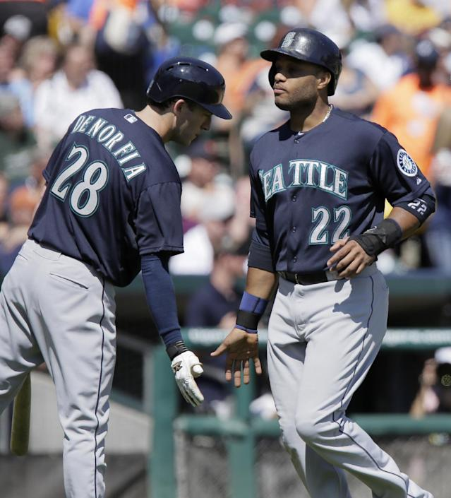 Seattle Mariners' Robinson Cano (22) is congratulated by Chris Denorfia (28) after scoring on a single by Kyle Seager during the sixth inning of a baseball game against the Detroit Tigers, Sunday, Aug. 17, 2014, in Detroit. (AP Photo/Duane Burleson)