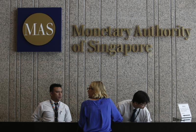 A visitor speaks to security officers at the building of the Monetary Authority of Singapore in Singapore