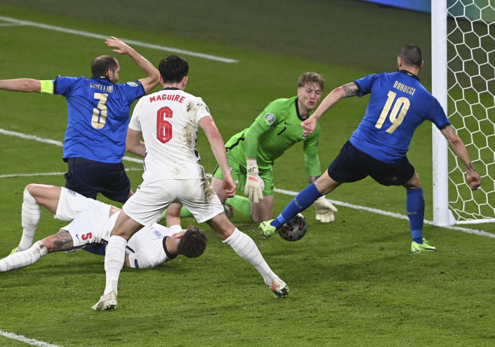 Italy's Leonardo Bonucci, right, scores his side's opening goal during the Euro 2020 final soccer match between Italy and England at Wembley stadium in London, Sunday, July 11, 2021. (Facundo Arrizabalaga/Pool via AP)