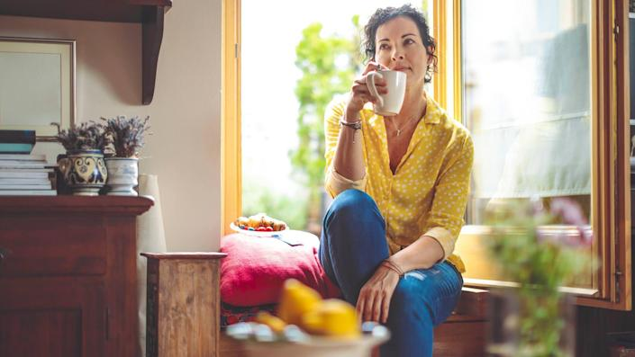 Mature woman is having the morning coffee at home.