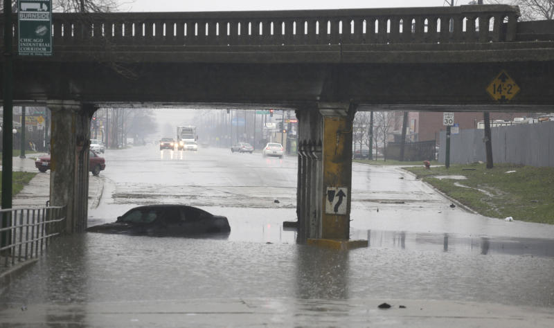 An abandoned car bobs in standing water under an overpass Thursday, April 18, 2013, in Chicago. Blasts of torrential rain and widespread flooding forced authorities to shut segments of major expressways, and hundreds of flights were scrapped. (AP Photo/M. Spencer Green)