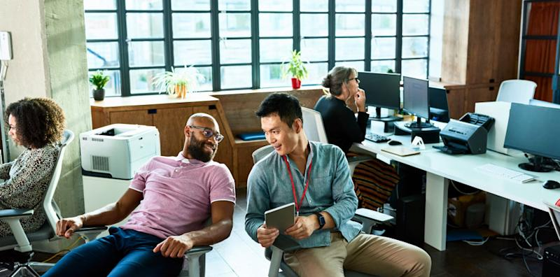 Two men chatting in office with digital tablet