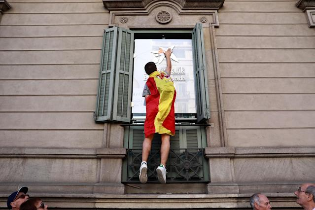 <p>A youth draped in a Spanish flag puts flag stickers on a Caixabank building before a mass rally against Catalonia's declaration of independence, in Barcelona, Spain, Sunday, Oct. 29, 2017. (Photo: Gonzalo Arroyo/AP) </p>
