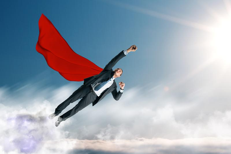 Wearing a red cape, a man in a suit flies above the clouds.