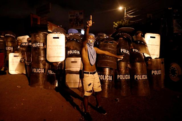 <p>A supporter of Salvador Nasralla, presidential candidate for the Opposition Alliance Against the Dictatorship, gestures in front of riot police while he waits for official presidential election results outside the warehouse of the Supreme Electoral Tribunal in Tegucigalpa, Honduras, Nov. 30, 2017. (Photo: Edgard Garrido/Reuters) </p>