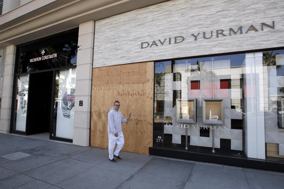 The entrance to the David Yurman store is boarded up on Rodeo Drive Monday, March 30, 2020, in Beverly Hills, Calif. Over the weekend, more people appeared to heed the message to stay home after beaches and many parks were closed by state and local officials following a swarm of visitors during the first weekend of the state's stay-at-home order in reaction to the coronavirus pandemic. (AP Photo/Marcio Jose Sanchez)