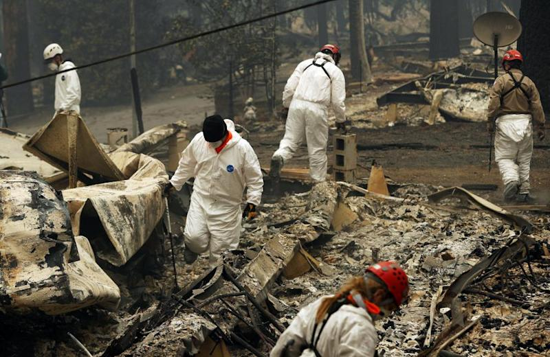 Rescue workers search for human remains at a trailer park burned out from the Camp fire in Paradise.