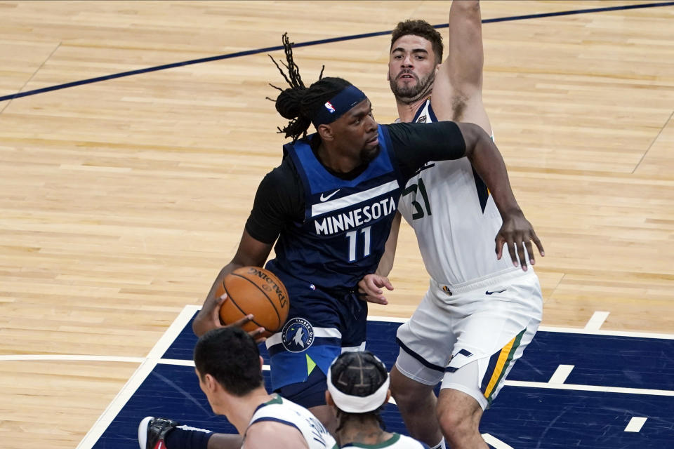 Minnesota Timberwolves' Naz Reid (11) drives on Utah Jazz's Georges Niang (31) in the first half of an NBA basketball game, Monday, April 26, 2021, in Minneapolis. (AP Photo/Jim Mone)
