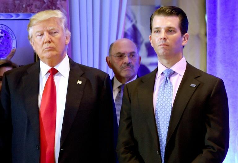 Then-president Donald Trump along with his son Donald, Jr., arrive for a press conference at Trump Tower in New York, as Allen Weisselberg (C), chief financial officer of The Trump, looks on January 11, 2017