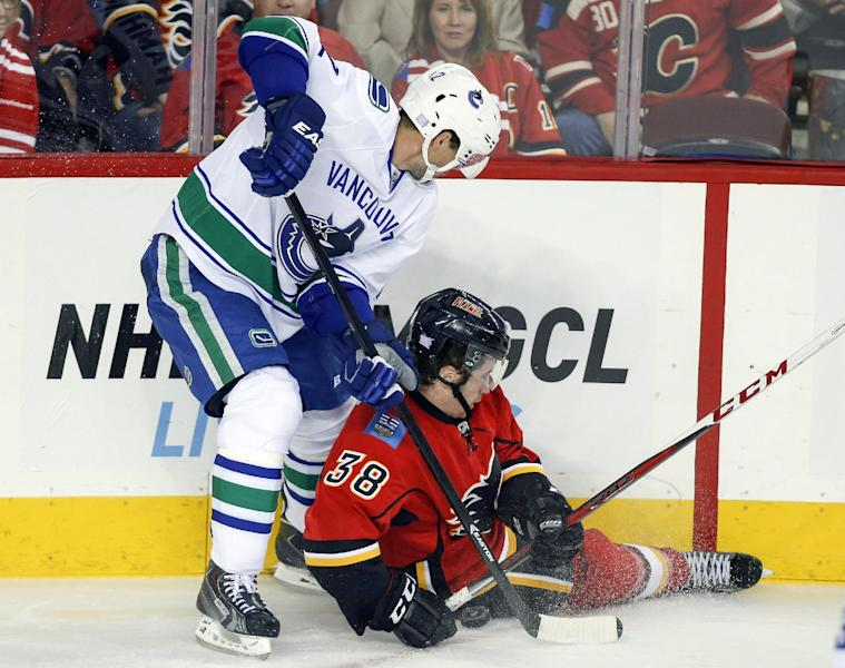 Vancouver Canucks' Dan Hamhuis, left, brings down Calgary Flames' Ben Street during first period NHL hockey action in Calgary, Alberta, Sunday, Oct. 6, 2013. (AP Photo/The Canadian Press, Jeff McIntosh)