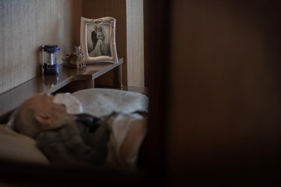 Leopoldo Roman, 85, lies in bed wearing a face mask as he waits for doctors during a home medical visit in Barcelona, Spain, April 3, 2020. Roman, whose leg was amputated years ago, has to pay for daily care out of his pension since the public system only provides for a social worker to come for an hour a day, three days a week. (AP Photo/Emilio Morenatti)