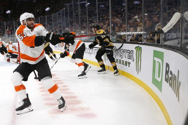 Philadelphia Flyers' Shayne Gostisbehere (53) tries to dislodge his stick after it became wedged in a joint in the glass during the first period of the team's NHL hockey game against the Boston Bruins in Boston, Sunday, Nov. 10, 2019. (AP Photo/Michael Dwyer)