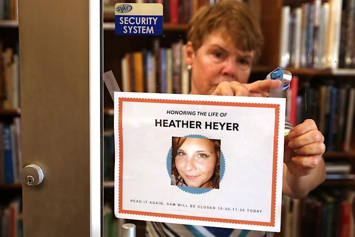 A persontapes a note to the front door of a bookstore to announce that it will close during the memorial service for Heather Heyer.