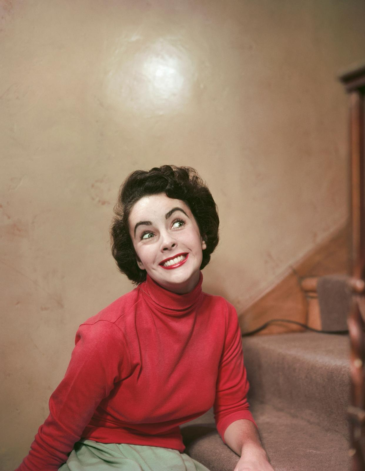The actress offers a big smileon a stairway in a red turtleneck, sometime in the '50s.