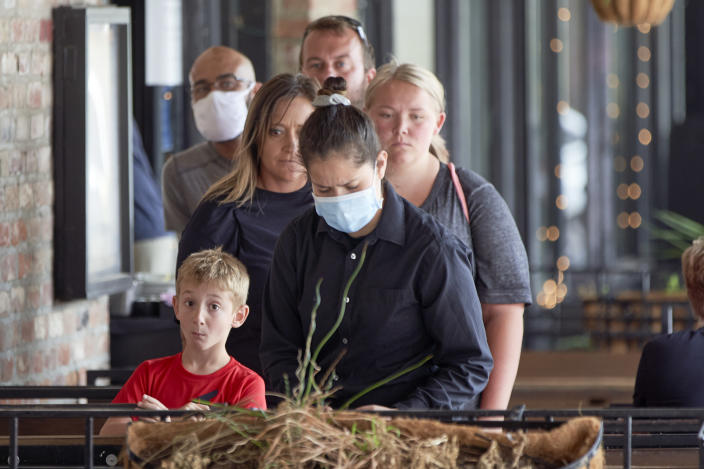 Diners wait for their waitress, center with face mask, to prepare their table at a restaurant in downtown Omaha, Neb., Friday, Aug. 7, 2020. (AP Photo/Nati Harnik)