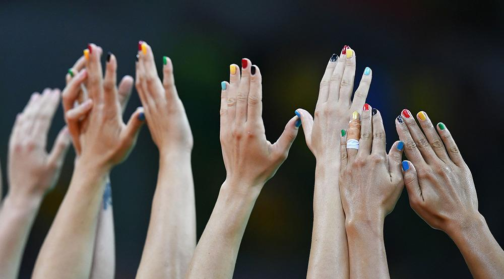 <p>Montenegrin players raise their hands during a women's handball match between Montenegro and Spain. (Photo: Getty Images)</p>