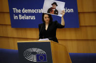 Belarusian opposition politician Sviatlana Tsikhanouskaya holds a picture of Belarusian opposition activist Nina Baginskaya as she gives a speech during the Sakharov Prize ceremony at the European Parliament in Brussels, Wednesday, Dec. 16, 2020. The European Union has awarded its top human rights prize to the Belarusian democratic opposition. (AP Photo/Francisco Seco)