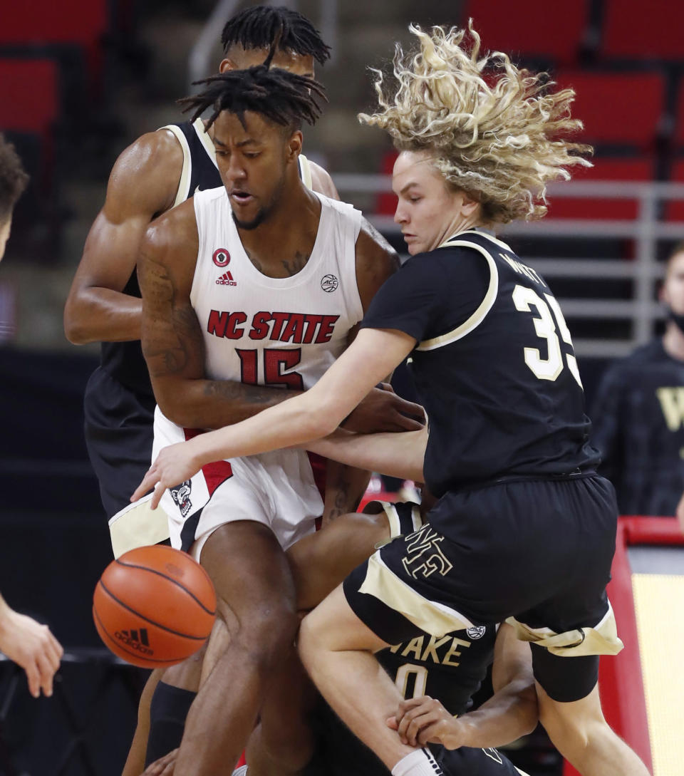 North Carolina State's Manny Bates (15) and Wake Forest's Carter Whitt (35) go for the ball during the first half of an NCAA college basketball game Wednesday, Jan. 27, 2021, in Raleigh, N.C. (Ethan Hyman/The News & Observer via AP, Pool)