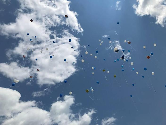 Balloons released by the friends and family of Paulette Thorpe fly above her memorial at Beechwood Cemetery in Durham on Sunday, July 4, 2021.