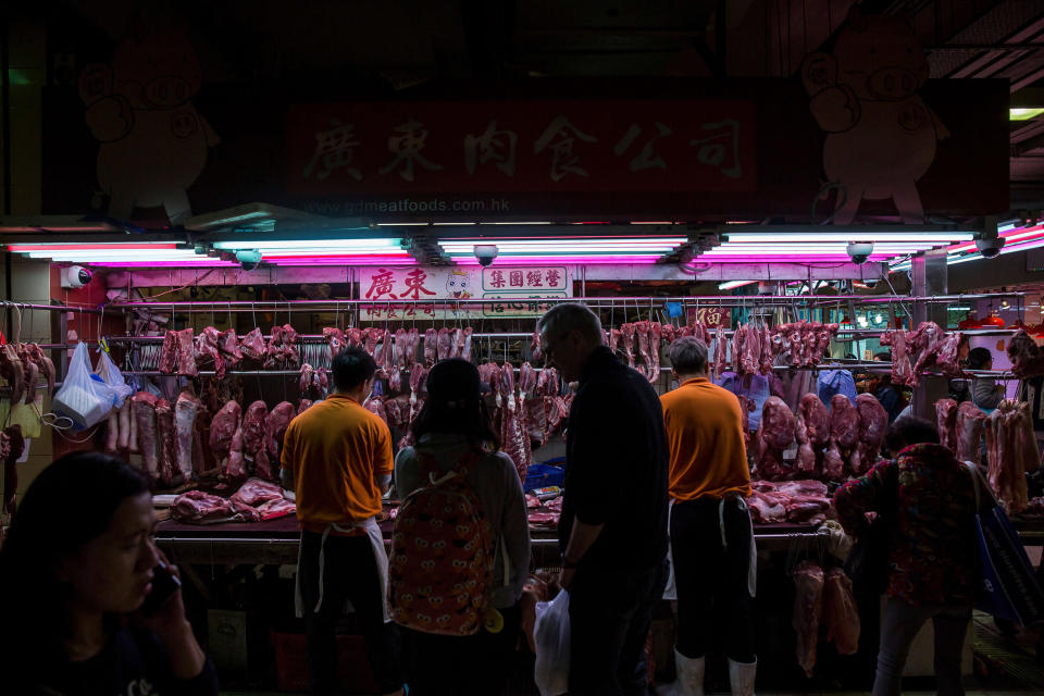 Image: Customers purchase pork from a stall at the Wan Chai wet market in Hong Kong. (Isaac Lawrence / AFP via Getty Images file)