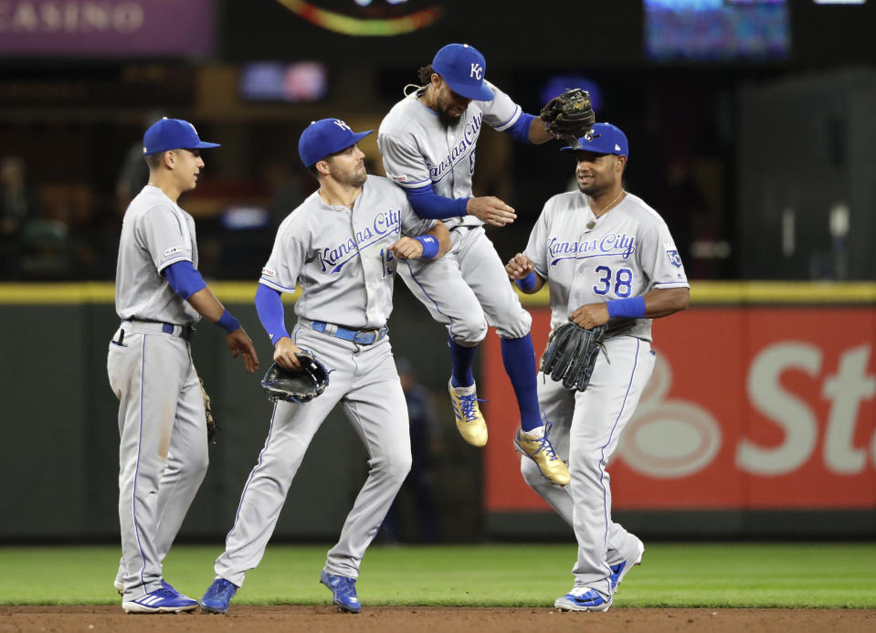 Kansas City Royals' Billy Hamilton (6) leaps against Whit Merrifield as they celebrate the team's 9-0 win over the Seattle Mariners in a baseball game Tuesday, June 18, 2019, in Seattle. (AP Photo/Elaine Thompson)