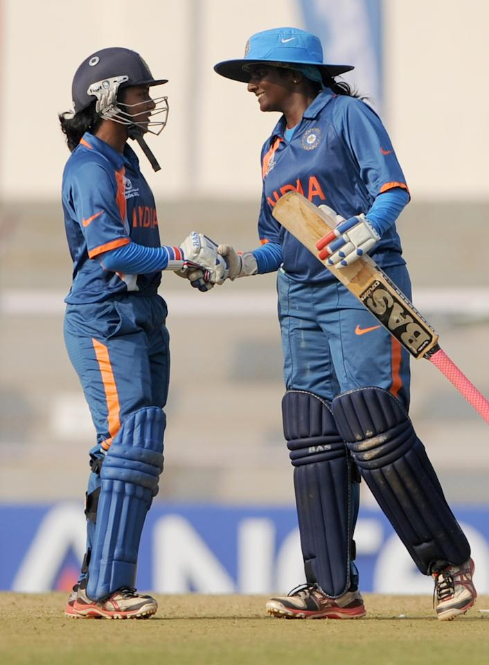 Indian cricketer Punam Raut (L) greets teammate Thirush Kamini after reaching her half century (50 runs)  during the inaugural match of the ICC Women's World Cup 2013 between India and West Indies at the Cricket Club of India's Brabourne stadium in Mumbai on January 31, 2013. Teams from Australia, England, New Zealand, Pakistan, South Africa, Sri Lanka, West Indies join hosts India for the global event which is being played from 31 January to 17 February.  The women's World Cup opened in Mumbai with the cricketers hoping to put aside memories of the unsavoury build-up and gain their due recognition in a country where the men's game reigns supreme. AFP PHOTO/ Indranil MUKHERJEE        (Photo credit should read INDRANIL MUKHERJEE/AFP/Getty Images)