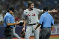 Boston Red Sox relief pitcher Josh Taylor gestures as home plate umpire Phil Cuzzi (10) checks his hat for any foreign substances after Taylor retired the Tampa Bay Rays during the seventh inning of a baseball game Tuesday, June 22, 2021, in St. Petersburg, Fla. Looking on is umpire Tom Hallion. (AP Photo/Chris O'Meara)