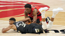 Milwaukee Bucks forward Giannis Antetokounmpo (34) fouls Toronto Raptors forward Stanley Johnson (5) as they battle for the ball during the second half of an NBA basketball game Wednesday, Jan. 27, 2021, in Tampa, Fla. (AP Photo/Chris O'Meara)