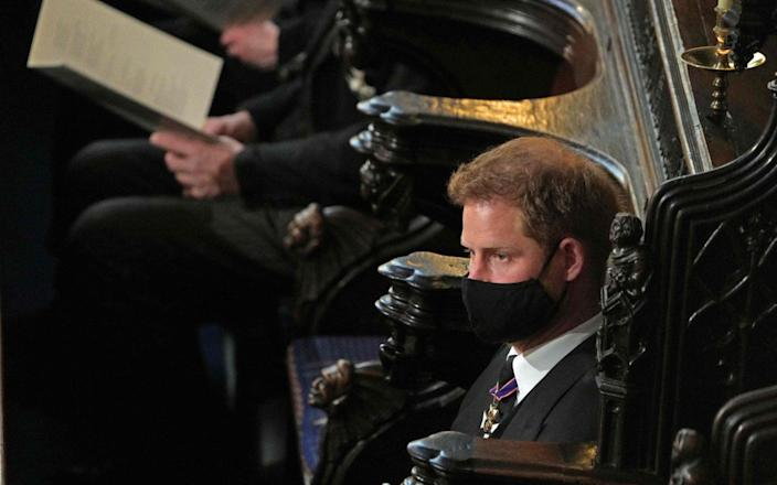 The Duke of Sussex was sitting on the other side of his brother during a ceremony at St. George's Chapel-AFP