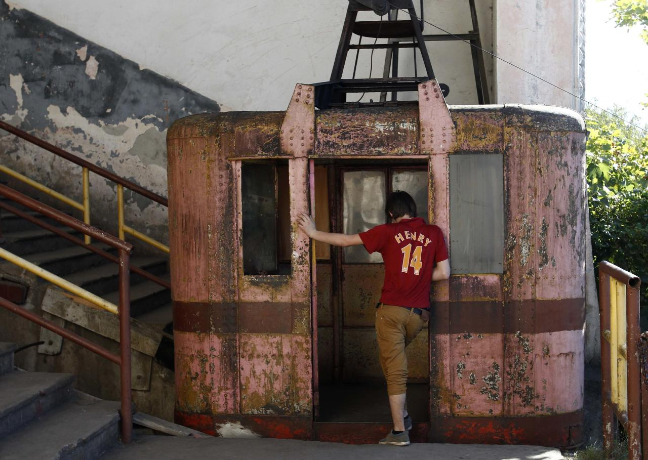A boy stands at the door of a 60-year-old cable car in the town of Chiatura, some 220 km (136 miles) northwest of Tbilisi, September 12, 2013. Dating to the Soviet era, Chiatura's public cable cars were built to facilitate the manganese mining industry, which formed the bedrock of the town's economy. Sixty years later, 15 of Chiatura's 21 cable car routes are still running, covering a total length of over 6000 meters, and they are still the quickest and most convenient way of getting around, despite their advanced years. Picture taken September 12, 2013. REUTERS/David Mdzinarishvili (GEORGIA - Tags: SOCIETY TRANSPORT TPX IMAGES OF THE DAY)  ATTENTION EDITORS: PICTURE 7 OF 31 FOR PACKAGE 'CHIATURA'S CRUMBLING CABLE CARS'.  SEARCH 'CHIATURA DAVID' FOR ALL IMAGES