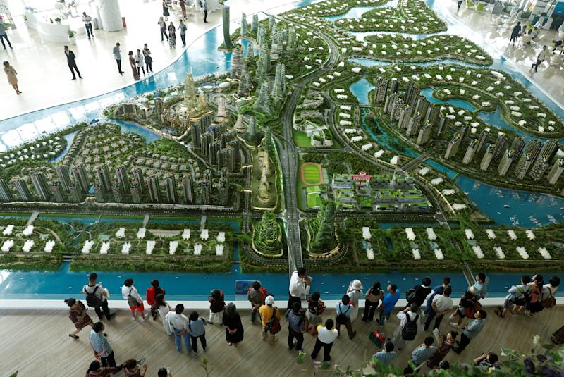 File photo showing prospects look at a model of the development at the Country Gardens' Forest City showroom in Johor Baru. — Reuters pic