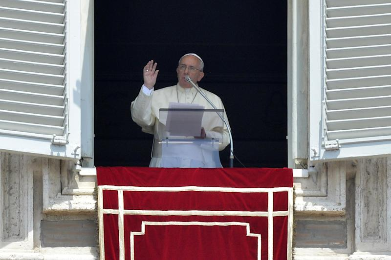 Pope Francis greets the crowd from the window of his apartments during the Sunday's Angelus prayer at St Peter's Square on July 20, 2014 at the Vatican
