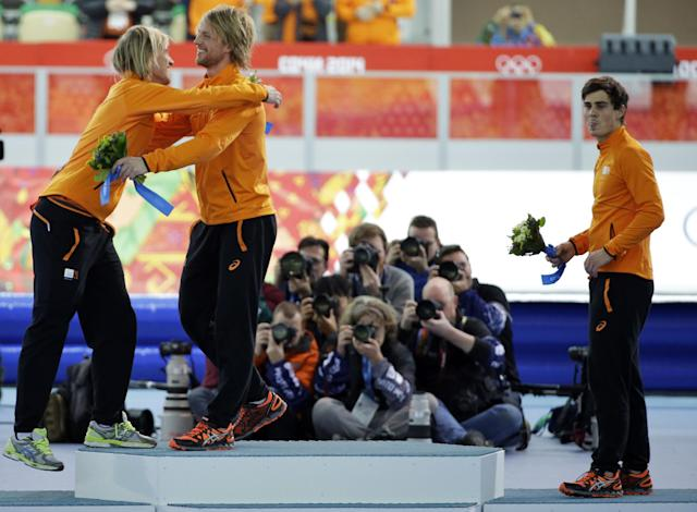 Twin brothers from the Netherlands, gold medallist Michel Mulder, second right, and bronze medallist Ronald, left, hug as silver medallist Jan Smeekens of the Netherlands, who lost the gold medal by 12 thousandth of a second, stands beside, in the men's 500-meter speedskating race at the Adler Arena Skating Center at the 2014 Winter Olympics, Monday, Feb. 10, 2014, in Sochi, Russia. (AP Photo/David J. Phillip)