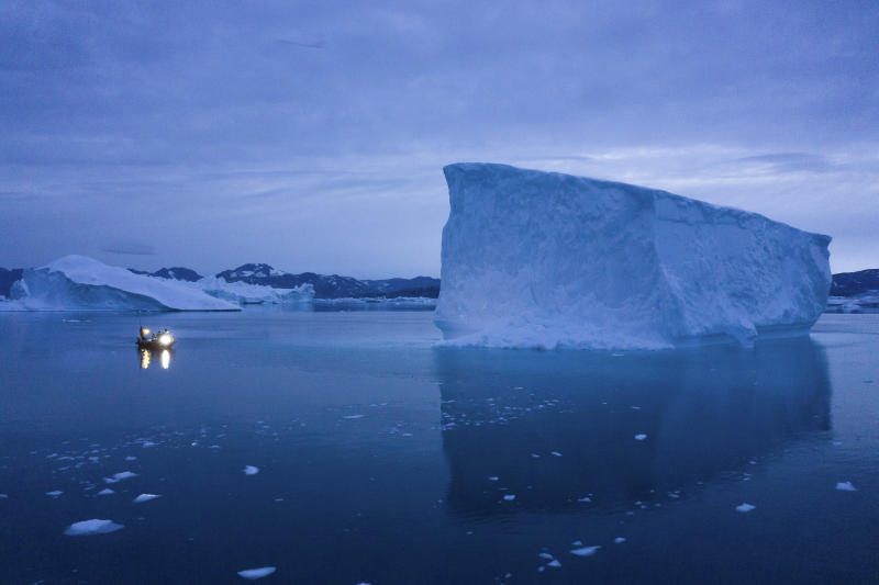 FILE - In this Aug. 15, 2019, file photo, a boat navigates at night next to large icebergs in eastern Greenland. As warmer temperatures cause the ice to retreat the Arctic region is taking on new geopolitical and economic importance, and not just the United States hopes to stake a claim, with Russia, China and others all wanting in. (AP Photo/Felipe Dana, File)