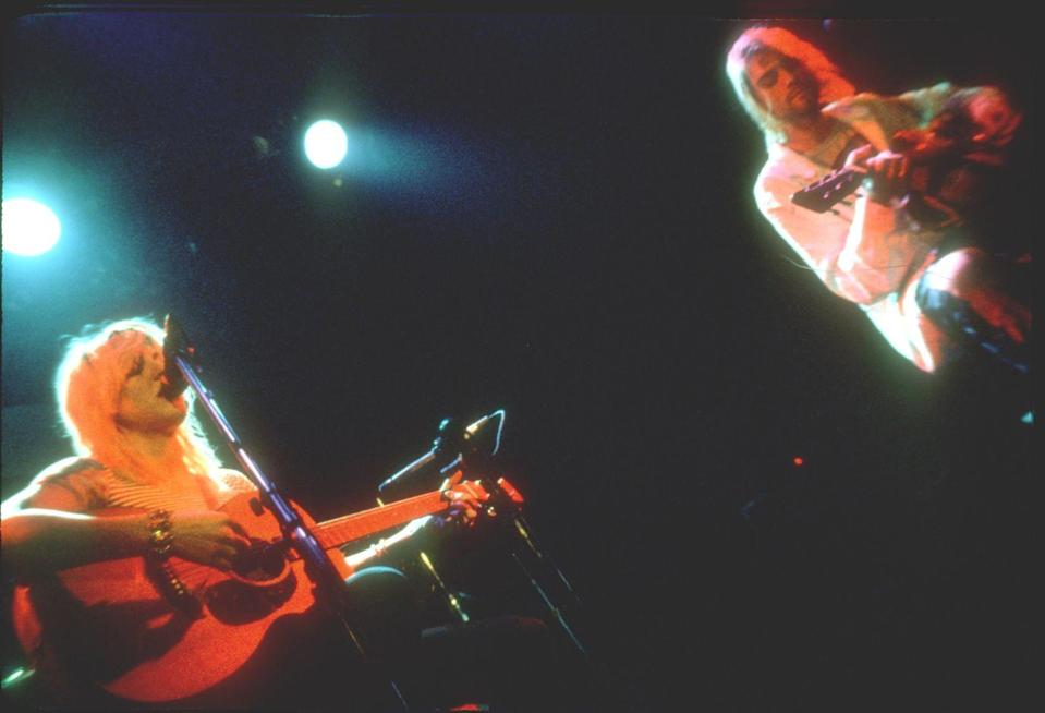 <p>Courtney Love and Kurt Cobain perform on acoustic guitars in 1993. </p>