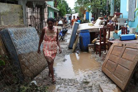 A woman walks in front of a house flooded by the overflow the Soco River in the aftermath of Hurricane Maria in El Seibo, Dominican Republic, September 22, 2017. REUTERS/Ricardo Rojas