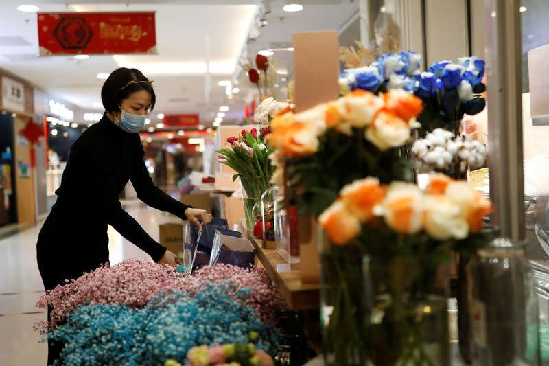 A florist who prefers to be called Cai Xiaoman wearing a face mask, works at a flowers shop in a shopping mall, as the country is hit by an outbreak of the new coronavirus, in Beijing