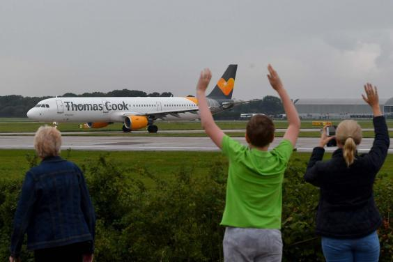 A pilot's family wave as a Thomas Cook plane departs from Manchester with the travel giant's future still uncertain (Getty)