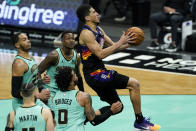 Phoenix Suns guard Devin Booker scores past the Charlotte Hornets during the second half of an NBA basketball game on Sunday, March 28, 2021, in Charlotte, N.C. (AP Photo/Chris Carlson)