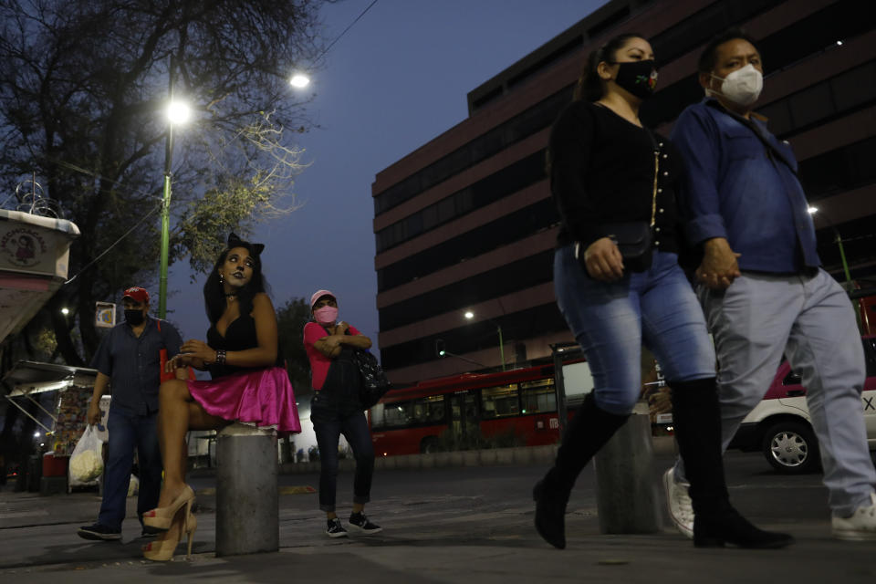 Sex worker Geraldine wearing cat make-up sits on her usual corner as she waits for clients outside the Revolution subway station, in Mexico City, Saturday, March 13, 2021. Geraldine, 30, a sex worker since age 15, says many of her regular clients have stopped coming amid the coronavirus pandemic and that seeing new clients presents new health and security risks. She is most concerned about the risk of bringing COVID-19 home to her partner, who has diabetes. (AP Photo/Rebecca Blackwell)