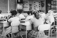 <p>A teacher gets a short break while the students focus on a lesson being delivered from the TV. </p>