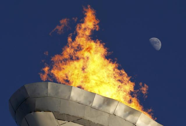 The Olympic cauldron's flame burns in the Olympic Park as the moon rises behind it at the 2014 Sochi Winter Olympics, February 8, 2014. REUTERS/Gary Hershorn (RUSSIA - Tags: OLYMPICS SPORT)